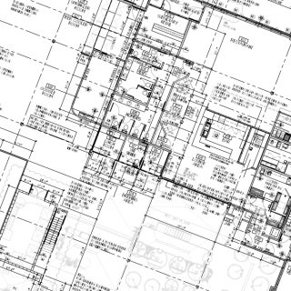 A set of commercial construction blueprints rotated at an angle.